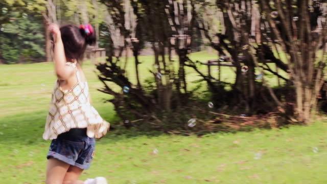 vídeos de stock, filmes e b-roll de feliz dois pequena garota brincando com bolhas de sabão ao ar livre, rindo e pulando. - festival tradicional