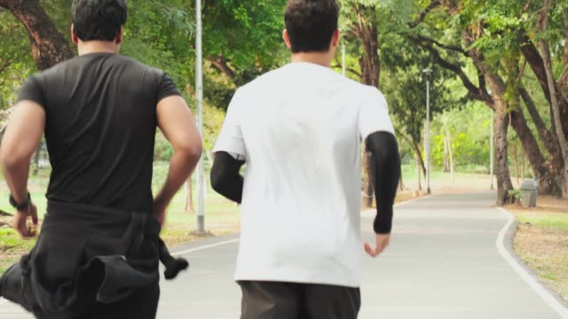 4k, happy two men friends and sports people jogging and running in public park. slow motion. - defeat stock videos & royalty-free footage