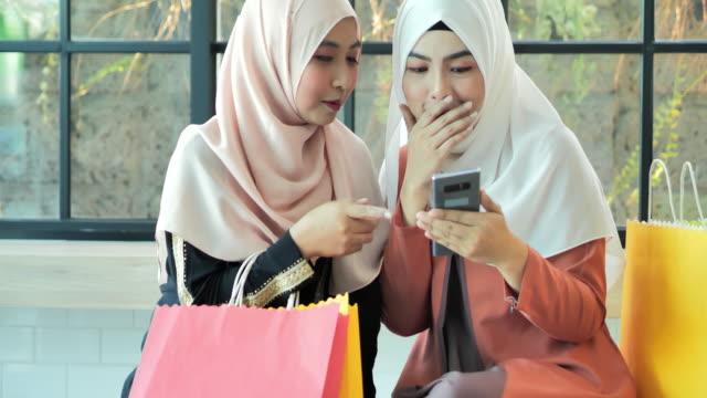 vídeos de stock, filmes e b-roll de mulheres muçulmanas dois felizes compras on-line. juventude árabe - etnia