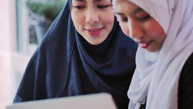 vidéos et rushes de heureux deux femmes musulmanes achats en ligne. jeune femme musulmane dans l'écharpe de tête utilisant l'ordinateur portatif dans le café avec des amis. jeunesse arabe - moyen orient