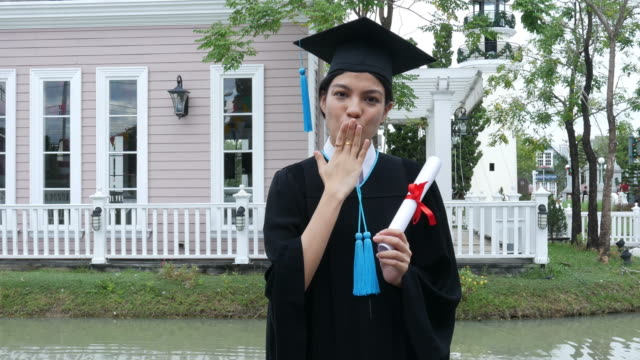 Happy university graduate with a diploma , blowing a kiss
