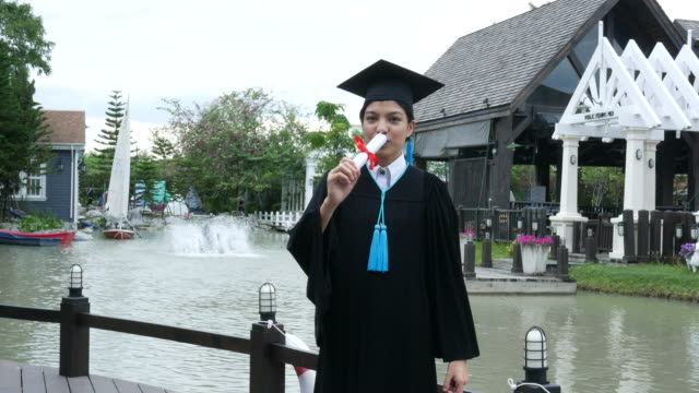 happy university graduate with a diploma , blowing a kiss - diploma stock videos and b-roll footage