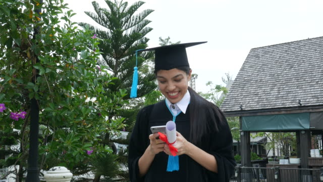 happy university graduate with a diploma , using phone - diploma stock videos and b-roll footage
