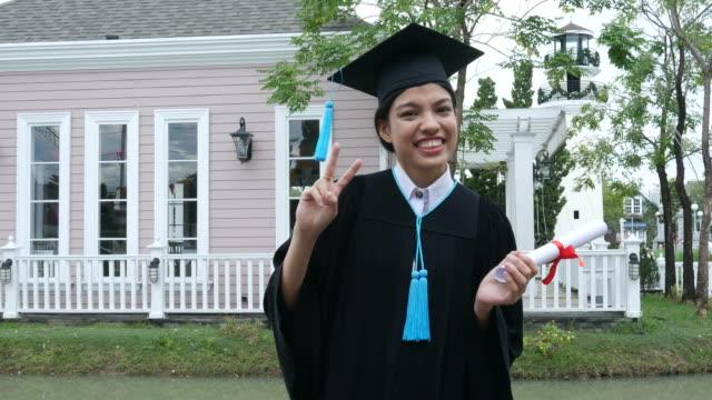 Glücklich Uni-Absolvent mit Diplom, Victory-Zeichen