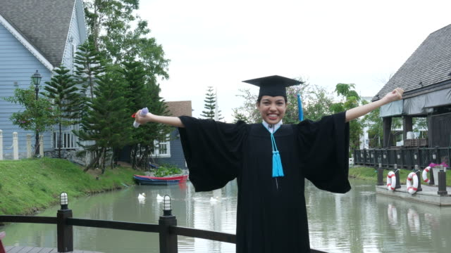 happy university graduate with a diploma - graduation gown stock videos and b-roll footage