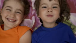 Happy Vlogger. Making Video Call. Friends Selfie. Excited Children Playing Lying on Bed and Taking Selfie. Little Brother and Sister Monkeying on Looking Camera.Taking Selfie Smartphone. Close up.