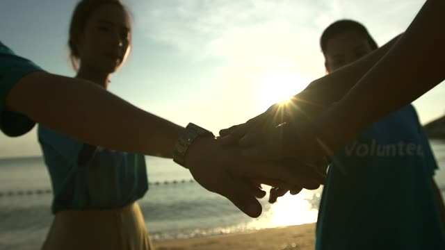vídeos y material grabado en eventos de stock de voluntarios felices de pie en la playa y haciendo círculo, unidad y concepto de colaboración - voluntario