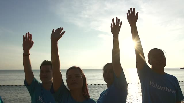vídeos de stock, filmes e b-roll de voluntários felizes que estão na praia e levantam sua mão, unidade e conceito da colaboração. - de braço levantado