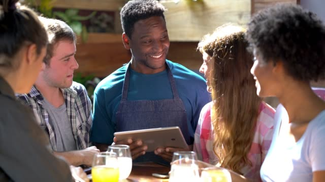 Happy waiter serving a group of friends and taking the order on a digital tablet