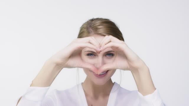 vidéos et rushes de heureuse femme clignotante fronces grâce à forme de coeur - personnes belles