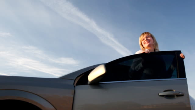 stockvideo's en b-roll-footage met happy woman against the car - uitstappen
