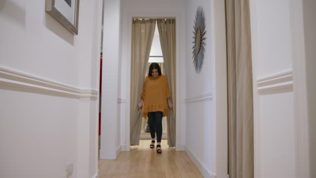 stockvideo's en b-roll-footage met gelukkige vrouw bij een kledingopslag die op een overmaatse blouse probeert die spiegel het glimlachen bekijkt - paskamer