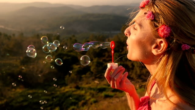 Happy woman blowing bubble on hill