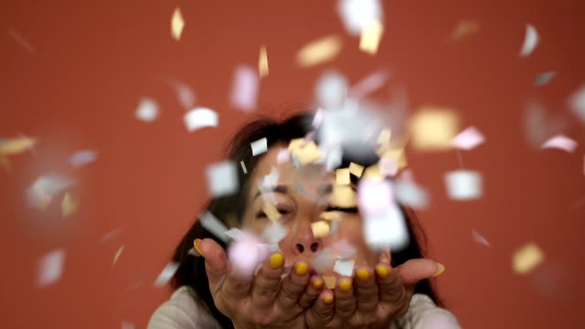 happy woman blowing confetti,celebrations concept - anniversary stock videos & royalty-free footage
