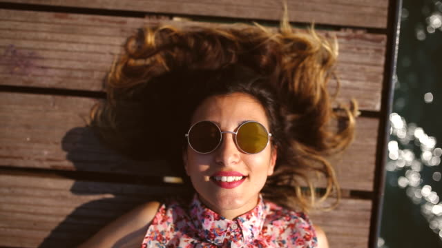happy woman by the sea - sunglasses stock videos & royalty-free footage