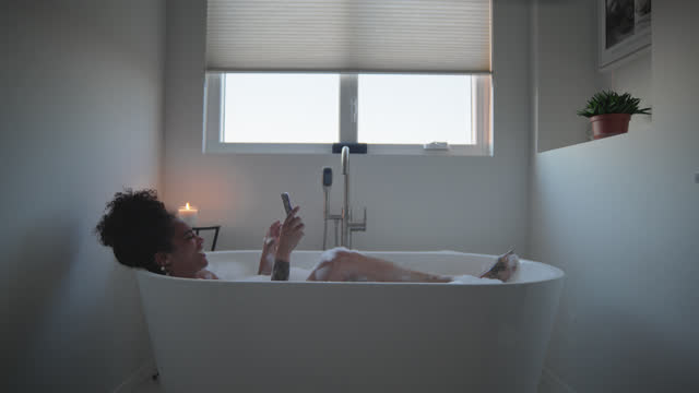 happy woman chats over a video call while she takes a bath - soap sud stock videos & royalty-free footage