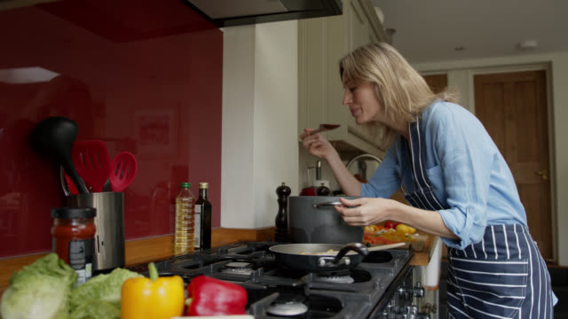 vídeos de stock e filmes b-roll de happy woman cooking dinner at home and tasting the food while smiling - provar