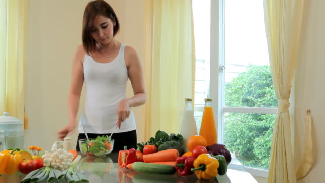happy woman cooking vegetables green salad - stereotypical housewife stock videos & royalty-free footage