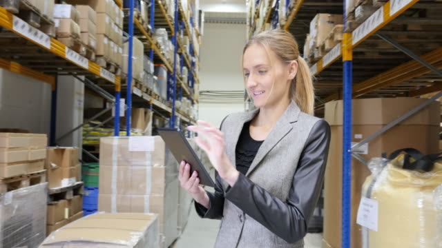 Happy woman counting stocks with digital tablet in warehouse
