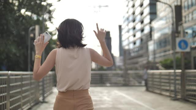 vídeos y material grabado en eventos de stock de mujer feliz bailando y saltando en bailes locos y divertidos afuera en la calle. - saltar actividad física