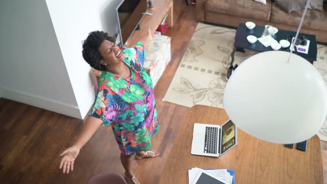 happy woman dancing at home in front of laptop during a virtual happy hour - live event stock videos & royalty-free footage