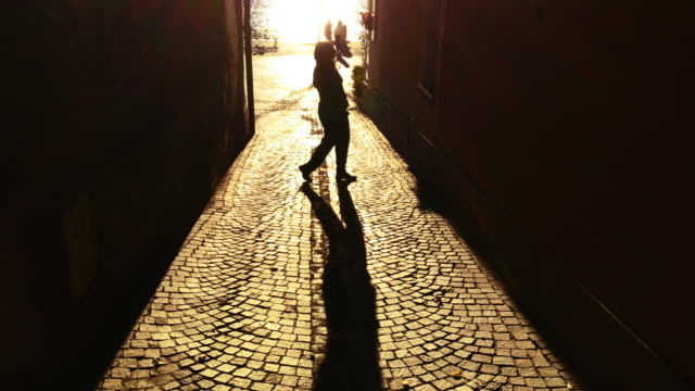 happy woman dancing in a narrow street with sunbeam and shadow - curiosity stock videos & royalty-free footage