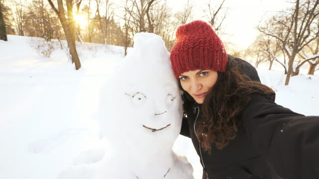 happy woman doing selfie with a snowman. - snowman stock videos & royalty-free footage