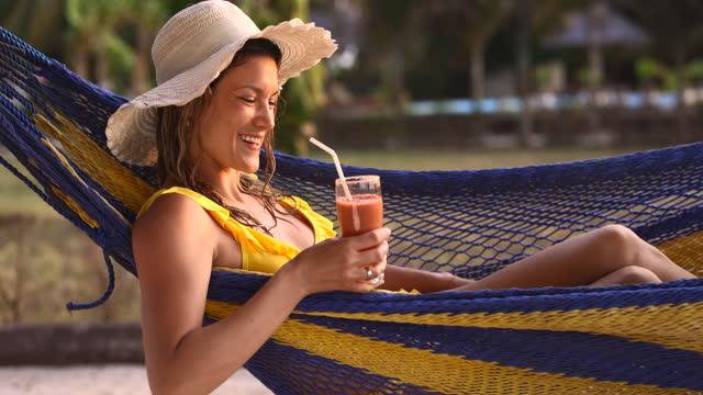 vidéos et rushes de smoothie potable heureux de femme pendant le jour d'été dans un hamac. - refreshment