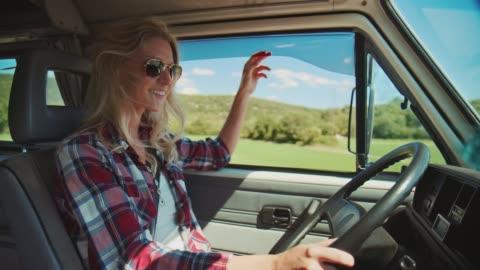 vidéos et rushes de fourgon heureux de conduite de femme pendant des vacances d'été - a la mode