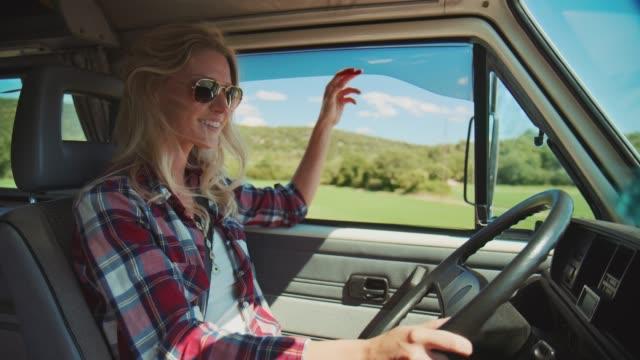 vidéos et rushes de fourgon heureux de conduite de femme pendant des vacances d'été - conduire