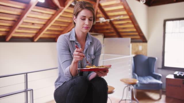 vídeos y material grabado en eventos de stock de happy woman eating her meal at home - happy meal