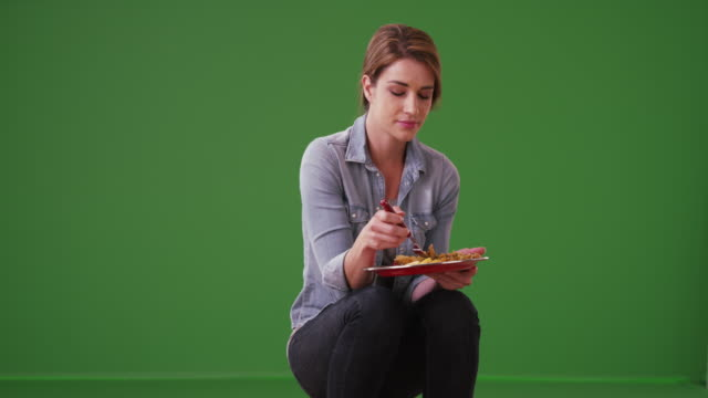 'happy woman eating her meal on green screen - happy meal stock videos & royalty-free footage