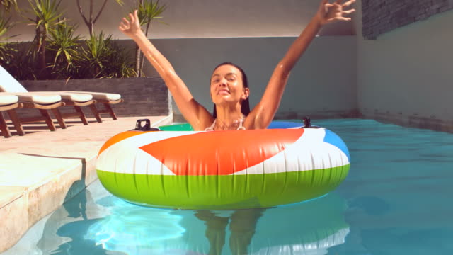 happy woman emerging from underwater into rubber ring in pool - freibad stock-videos und b-roll-filmmaterial