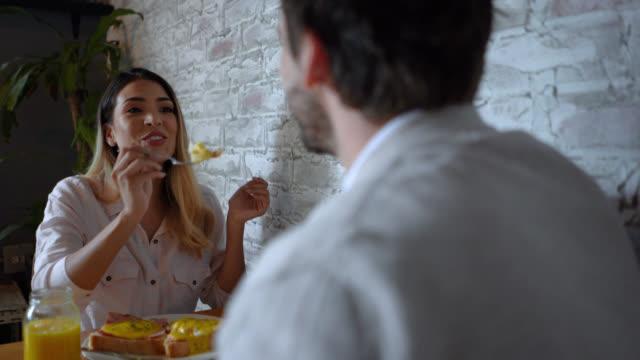 vidéos et rushes de femme heureux appréciant son petit déjeuner avec le associé à un restaurant tout en parlant - partage
