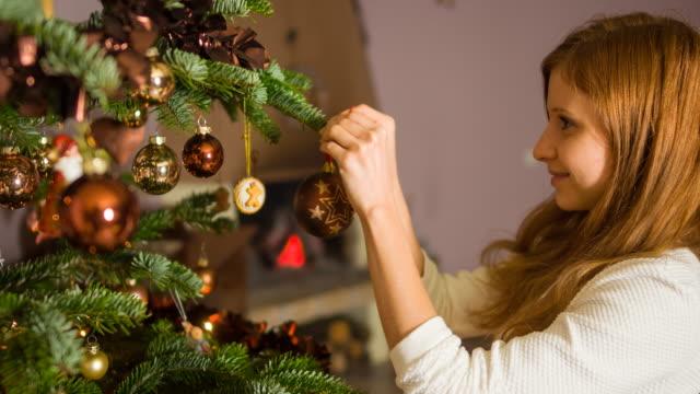 クリスマス ツリーを飾る仕上げ幸せな女 - ティンセル点の映像素材/bロール