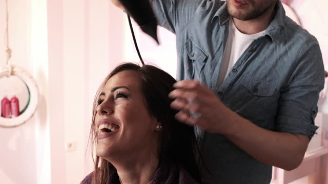 happy woman getting her hair dried at hair salon. - beauty salon stock videos and b-roll footage
