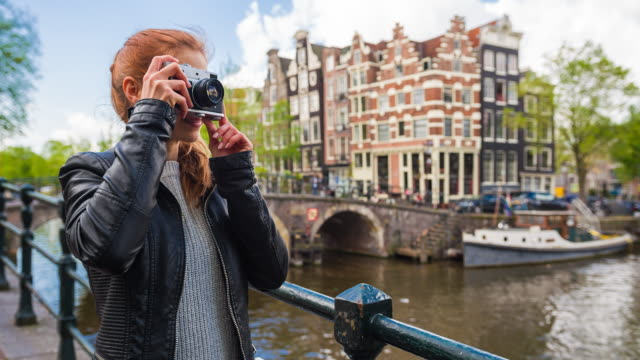 happy woman hipster tourist vacationing in amsterdam, taking pictures with retro camera - photographing stock videos & royalty-free footage