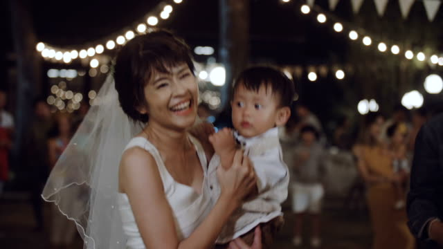 Happy woman holding and playing with her son at wedding party.