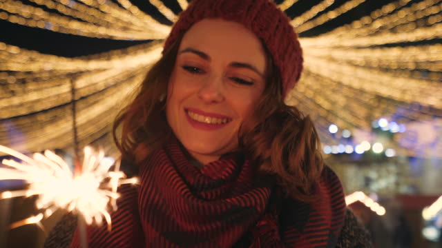 happy woman holding burning sparkler. - christmas market stock videos & royalty-free footage