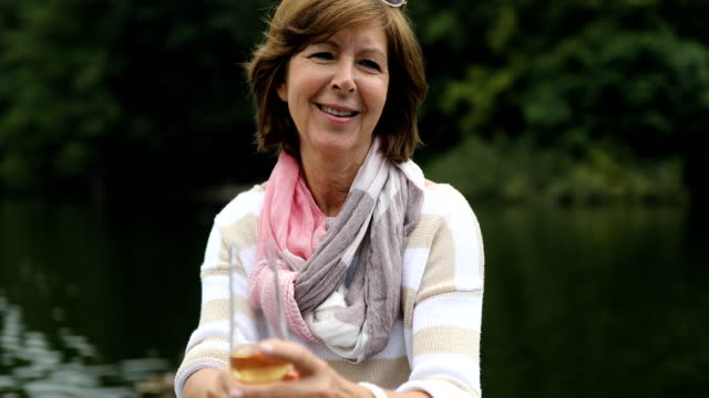 Happy woman holding champagne flute while boating