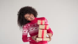 Happy woman holding Christmas gift boxes