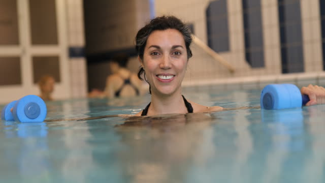 Happy woman holding dumbbells in swimming pool