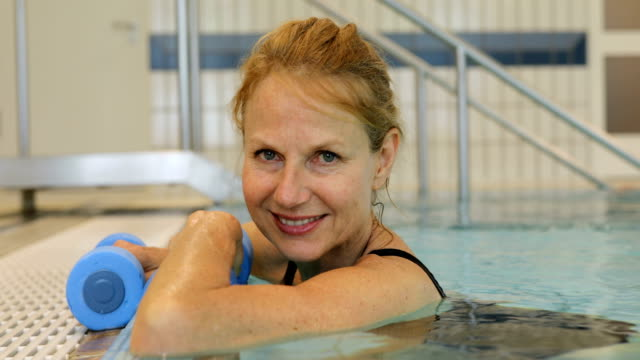 happy woman holding dumbbells in swimming pool - hydrotherapy stock videos & royalty-free footage