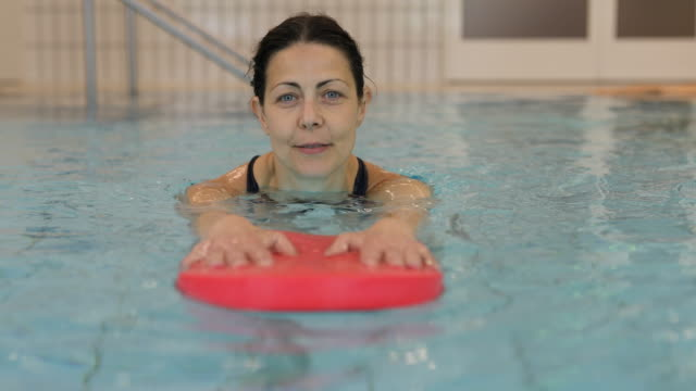 happy woman holding float while exercising in pool - hydrotherapy stock videos & royalty-free footage