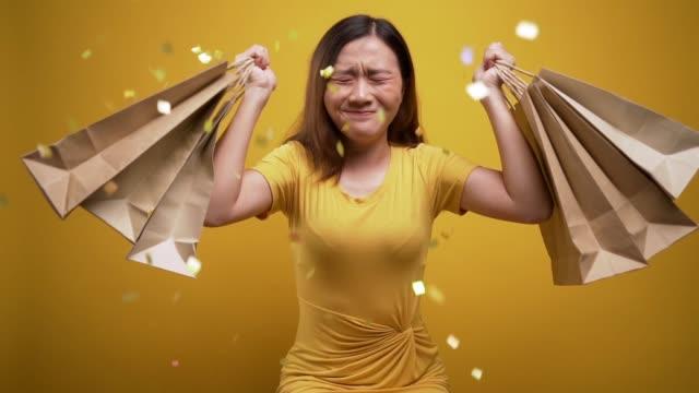 Femme heureuse retenant des sacs de magasinage sur le fond jaune isolé