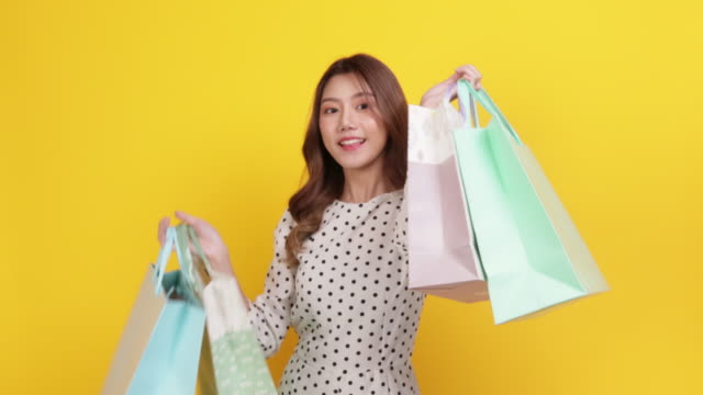 happy woman holding shopping bags over yellow background - yellow background stock videos & royalty-free footage