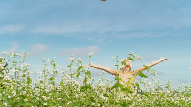 hd dolly slow-motion: happy woman in a buckwheat field - hat stock videos & royalty-free footage