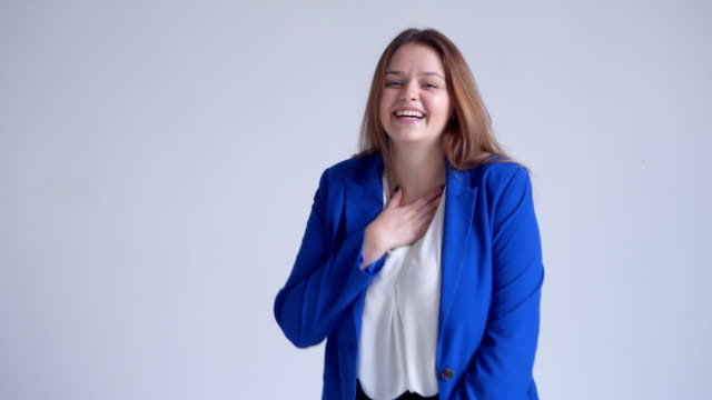 Happy woman in blue jacket laughing at camera