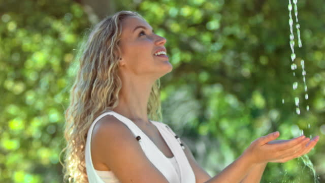 vídeos y material grabado en eventos de stock de happy woman in slow motion catching water - manos ahuecadas