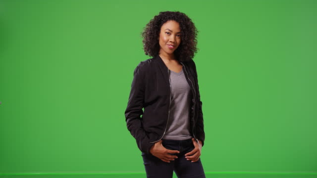 Happy woman in stylish black bomber jacket and jeans smiling on green screen